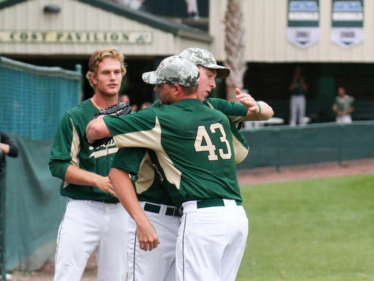 Freshman pitcher Brian Holcomb (43) gets a hug from a Jacksonville University teammate after pitching in his first college baseball game for the Dolphins against Georgia Southern on April 28 in Jacksonville. Holcomb, who is an active duty member of the U.S. Navy, started the game and pitched to one batter and gave up a single before being removed from the game to a standing ovation.