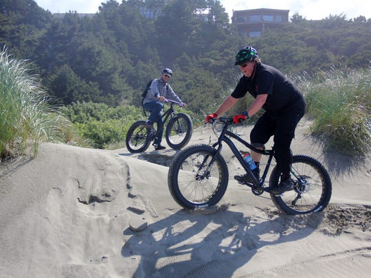 Elliott Crowder and Gay Urness ride some dunes with their fat bikes on the Oregon Coast's Nye Beach area in Newport.