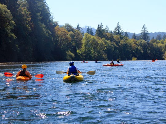 A group of kayakers head downstream through the changing colors of the North Santiam River.