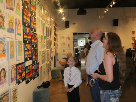 Carl Lym, 8, with his parents Summer and Valdean Lym at the VVAA reception at the Mesquite Art Gallery.