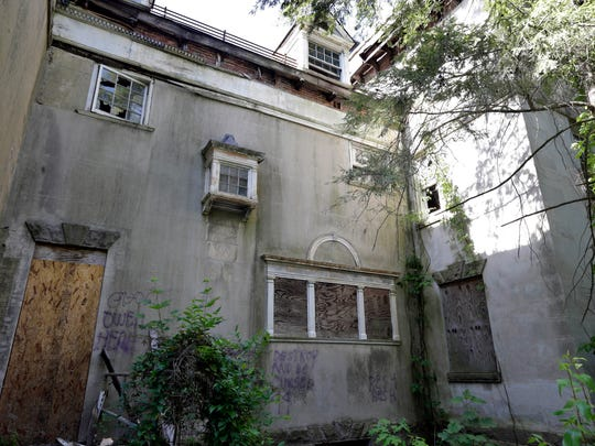 """Paint next to a boarded door says, """"Ghosts dwell here,"""" at a mansion built for industrialist Andrew McNeal in Burlington City. After decades of neglect, it's facing almost certain demolition."""