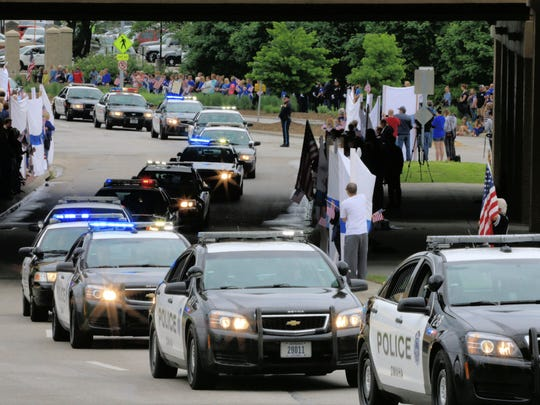 Crowds line the path of the funeral procession of Omaha Police Officer Kerrie Orozco in Omaha on Tuesday. Orozco was shot to death on May 20 while trying to arrest a fugitive who was in turn fatally shot by another officer.