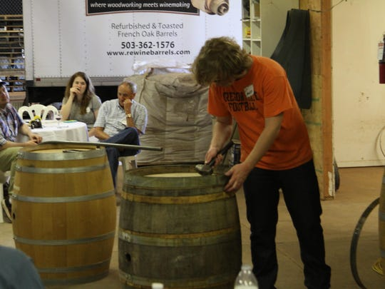 Matt Stickle, cellar master at Alexana Winery, tries his hand at removing a barrel head during a workshop at the reWine open house.