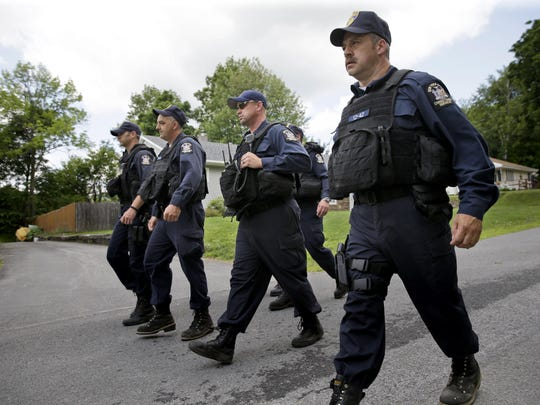 Law enforcement officers walk the streets in Dannemora, N.Y., as they searched houses near the maximum-security prison in northern New York where two killers escaped using power tools,Wednesday, June 10, 2015. State Police said the fifth day of searching will entail going from house to house in Dannemora, where David Sweat and Richard Matt cut their way out of the Clinton Correctional Facility.