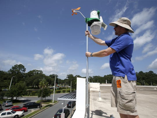 Luke Hunnewell, Director of Infrastructure for WeatherSTEM, installs a weather station on the roof of FAMU DRS High School recently. WeatherSTEM is placing weather stations in schools to teach students about rainfall, moisture and weather conditions.