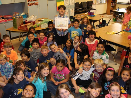 "Pharoah Castaneda stands with his classmates at Harritt Elementary School and holds an SJ Kids cartoon on June 5, 2015, inspired by his response to the question ""Why does hair turn gray?"""