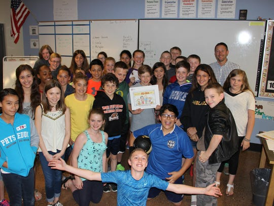 "Ben Zuk poses with his class at Straub Middle School, June 5, 2015. Zuk was presented with an SJ Kids cartoon inspired by his response to the question ""If you could make a new holiday, what would it be and how would you celebrate it?"""