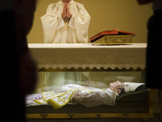 The Rev. John McLoughlin, pastor of Our Mother of Perpetual Help in Ephrata, Pa., prays over the remains of St. John Neumann at the national shrines of St. John Neumann in Philadelphia.