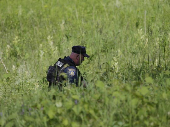 A New York State officers searches for convicted murderers Richard Matt and David Sweat, Friday, June 26, 2015, in Malone, N.Y. Matt, one of two convicted murderers who staged a brazen escape from an upstate maximum-security prison three weeks ago was shot and killed by a Border Patrol agent in a wooded area about 30 miles from the prison on Friday, while Sweat remains on the run. (AP Photo/Mary Altaffer)