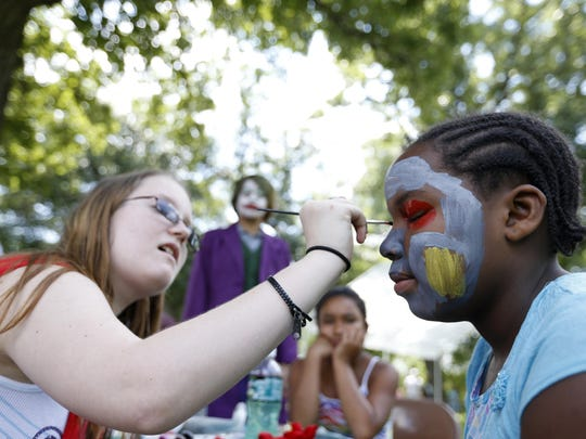Tristan Hoing, left, paints Karma Stanberry's face June 27 during Taking Back Waterloo's Hometown Heroes event at Exchange Park in Waterloo.