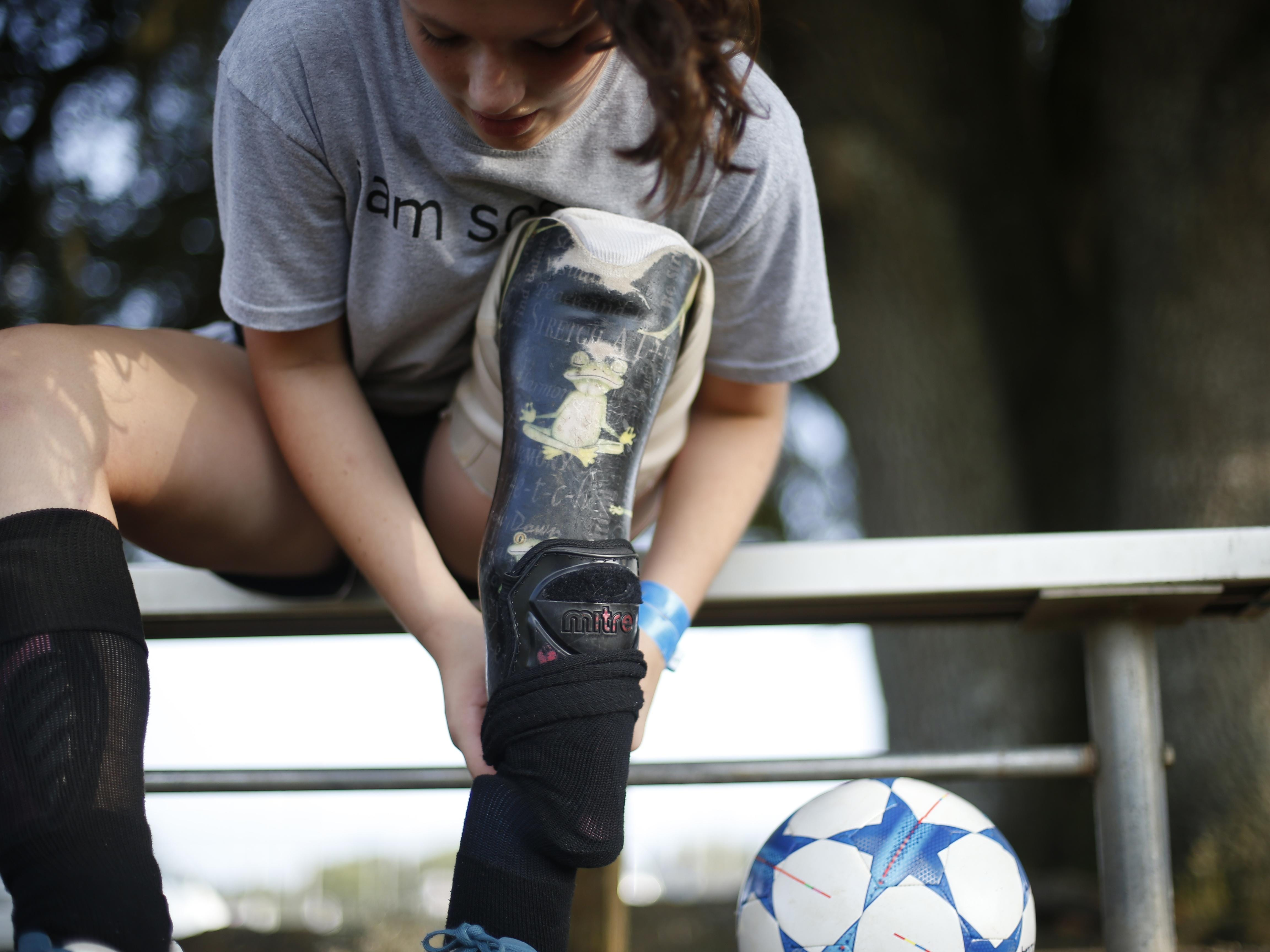 Erica Silvey, 13, covers her prosthetic leg with padding to protect her competition before practice with the Tottenham Hotspur Tallahassee 15U Select team she joined for the summer.