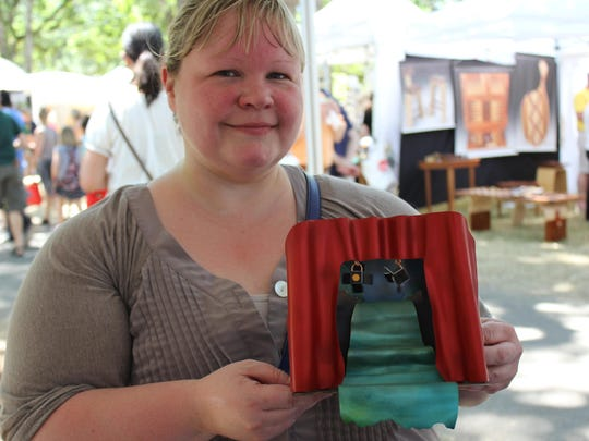 """Jenni Bertels shows a piece by Mandy Allen called """"Rushing Through the Scene."""" Photographed July 18, 2015 at the Salem Art Fair & Festival at Bush's Pasture Park."""