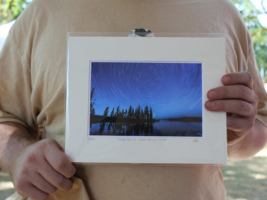 """Tyler Frederick liked the swirling stars of this print, """"Star Trails over Waldo Lake,"""" by Tim Giraudier. Photographed July 18, 2015 at the Salem Art Fair & Festival at Bush's Pasture Park."""