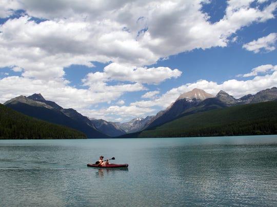 A kayaker paddles across Bowman Lake in Glacier National Park.