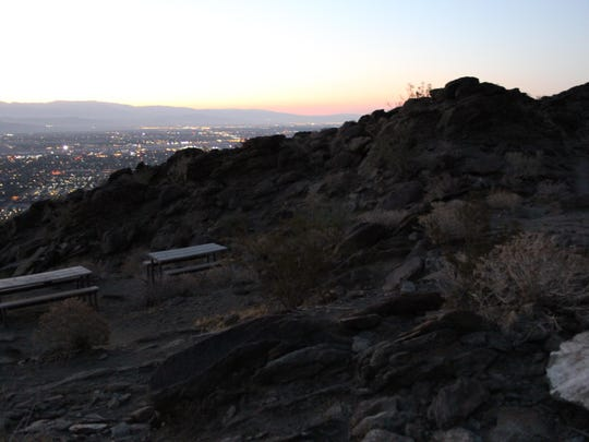 The sun rises beyond the picnic tables on the Skyline Trail in Palm Springs. Many make it up the relatively short, steep hike to the tables just above the Palm Springs Art Museum.