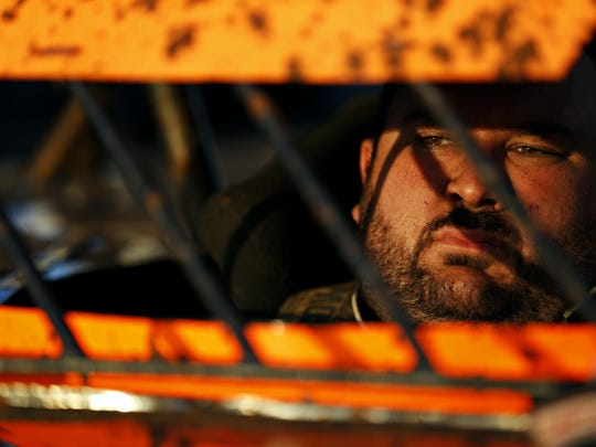 Mickey Burrell takes a moment in his car as he prepares to take the dirt track for a qualifying heat at the Springfield Raceway in Springfield, Mo. on June 21, 2015.