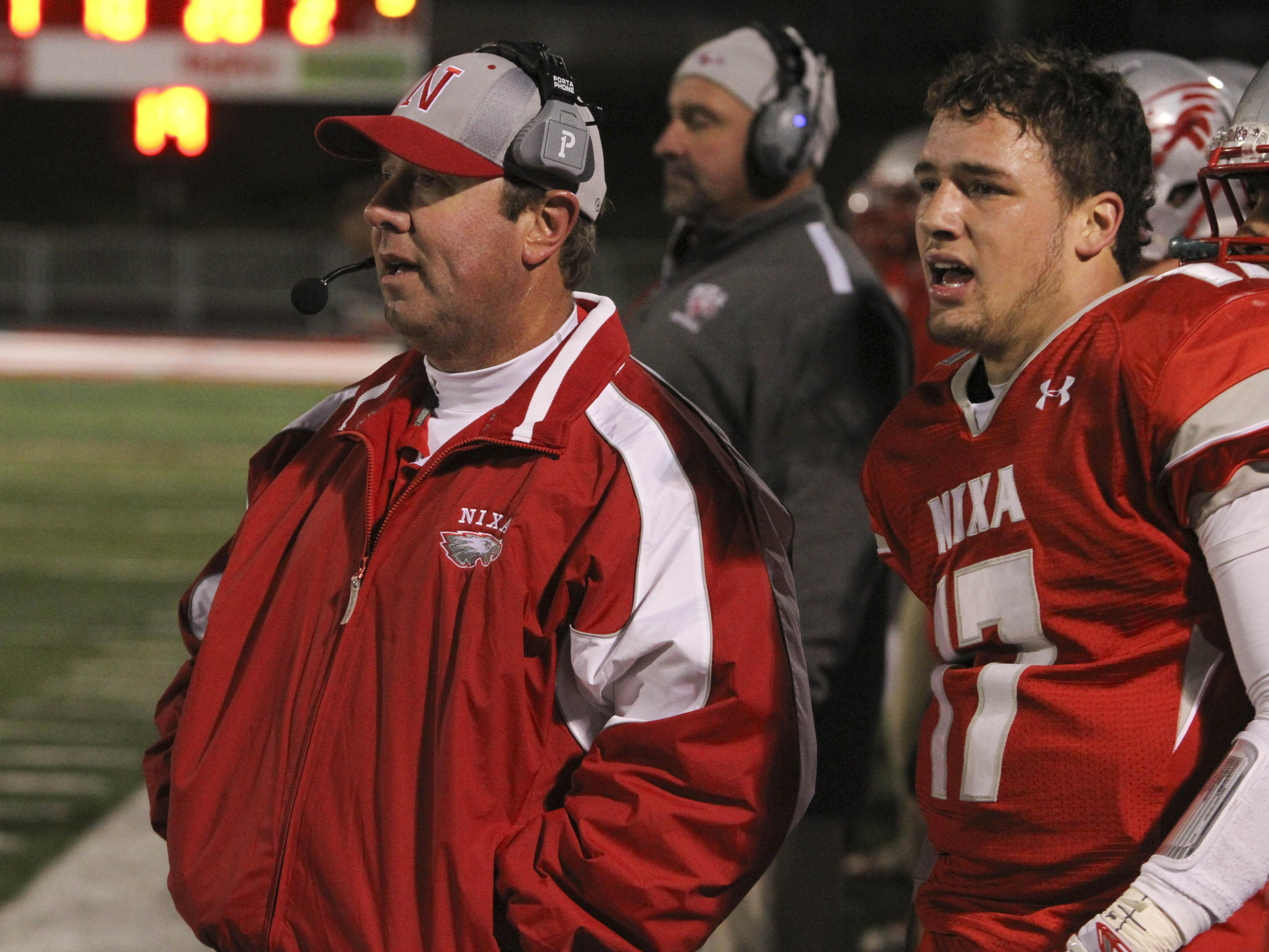 From left, Nixa football coach Richard Rehagen and QB/S Logan Tyler on the sideline at Eagle Stadium during a 2014 game.