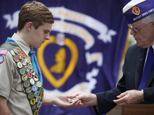 Life Scout Travis Hoffmann is given an honorary badge of recognition by Major John L. Haynes of the Military Order of Purple Hearts.