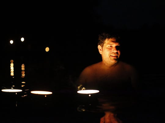 Dustin Nelson swims under the light of floating candles during Tallahassee Naturally's moonlight skinney dipping event at Suntan Lake on Friday, July 31, 2015.