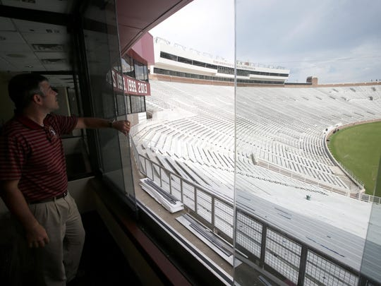 Stuart Pearce, Assistant Director of Event Management for FSU and coordinator of home football game operations, opens the new sliding glass windows on the lower-level suites, one of the new upgrades at Doak Campbell Stadium.