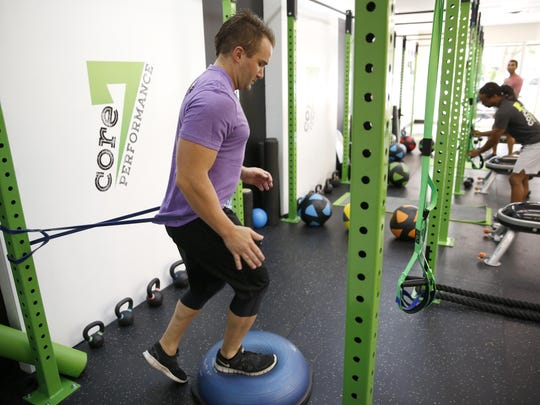 Will Duran steps on a BOSU ball while strapped to the apparatus that makes up Core 7's performance work out at the Fit & Functional gym on Thursday, Aug. 6, 2015.