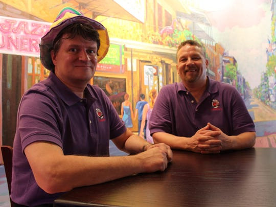 J. Gumbo's owners — John Jacobs, left, and Keith Malwitz, right — sit in front of a wall mural depicting New Orleans in their restaurant.