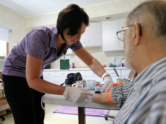 Nurse Kerri Lutjens draws blood from a Hutterite during a home visit at the Tschetter Colony near Olivet, S.D., Thursday, Aug. 13, 2015. Lutjens has spent the past few years gaining the trust of several communities of Hutterites, a deeply religious people, who live in insular farming communities in the Plains, Upper Midwest and Canada.
