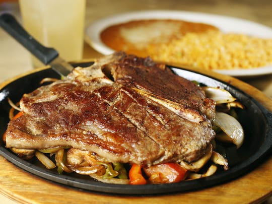 The T-bone steak at Los Tres Amigos Mexican Restaurant in Waukee comes with grilled onions, peppers and tomatoes and a side of rice and beans.