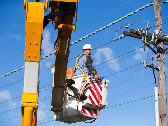 Dave Bennett, of the New Castle Municipal Services Commission, works on a power line on Aug. 13.