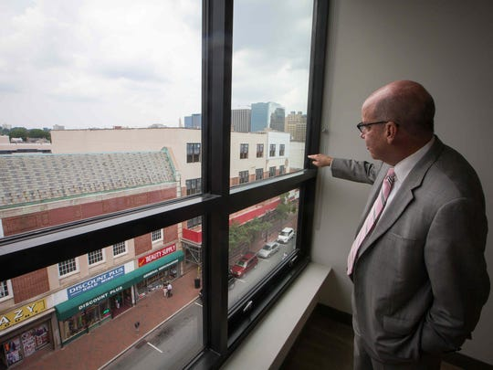 Michael Hare is a senior vice president with developer Buccini/Pollin Group. In this photo, he looks outside of a unit at 608 Market St. in downtown Wilmington.