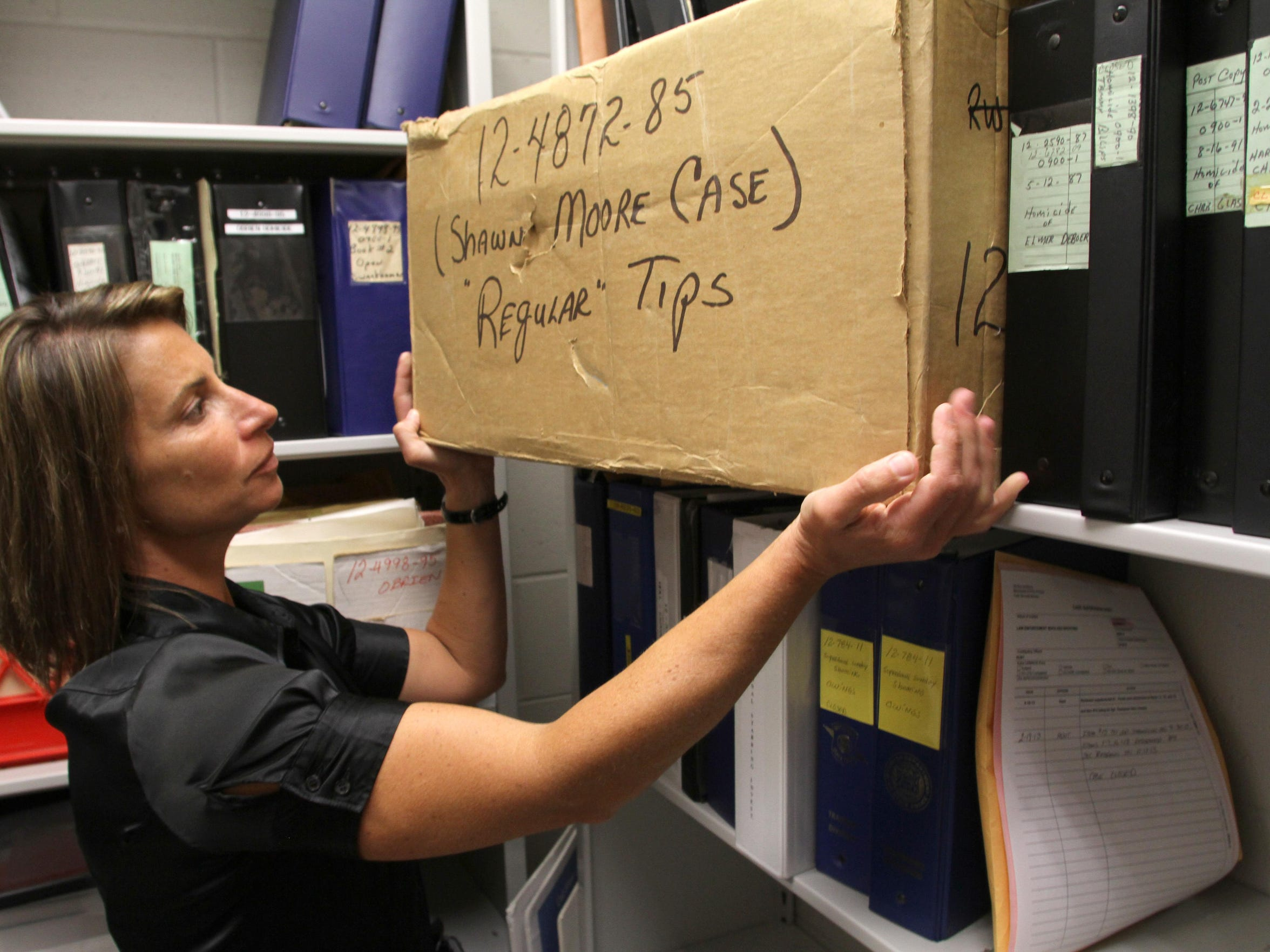 Michigan State Police Sgt. Angela Hunt of the Brighton Post shows the box containing between 1,600 and 2,000 tips from the 1985 investigation into the kidnapping and murder of 13-year-old Shawn Moore, of Green Oak Township.