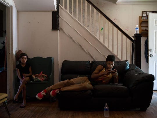Jaden Surratte, 14, sits in his home playing video games.
