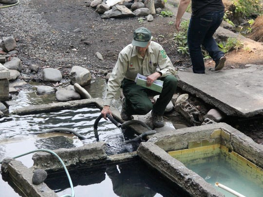 Grady McMahan, district ranger with Willamette National Forest, inspects on of the hoses used to pipe water at Lower Breitenbush Hot Springs northeast of Detroit.