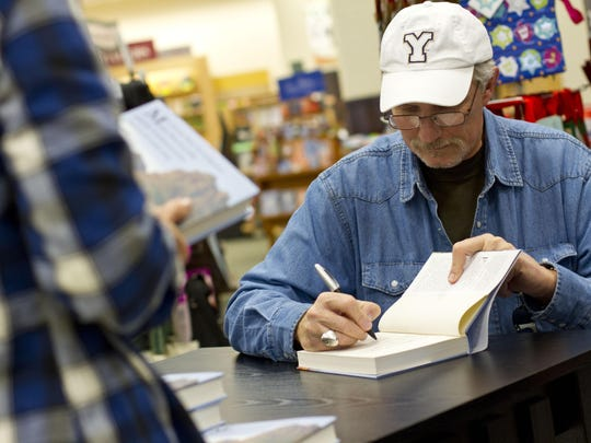 """Author Sam Brower signs a copy of his book, """"Prophet's"""