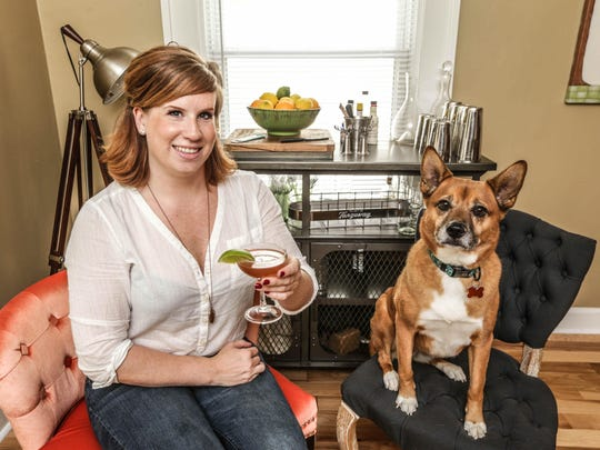 Kendall Lockwood, Lead Cocktologist & General Manager at the Ball & Biscuit, holds a daiquiri she created at her home, with dog Zoey.