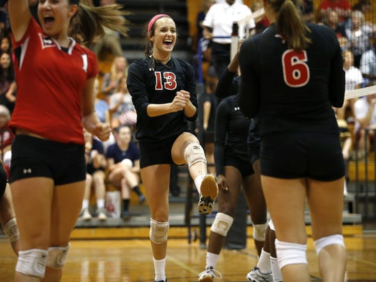 Leon's Jaynie Mitchell, center, celebtrates with with teamates after they won a point in their match against Chiles High School on Thursday.