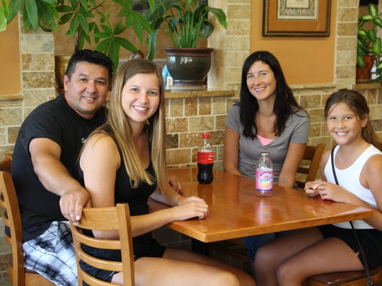 Tabor Pizza co-owner Kemal Andican, left, with daughters, Cayla and Jenna, and wife, Kim, second from right.