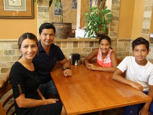 Tabor Pizza co-owner Ozzie Andican is seated with his wife, Sonia, left, daughter Henna, and son Emre, right.