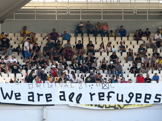 Syrian refugees, invited by AEK Athens' fans, sit behind a banner while watching the soccer match between AEK Athens and PAS Giannena for the Greek Soccer League at the Olympic stadium of Athens, Sunday, Sept. 13, 2015. At least 28 people seeking a better life in Europe drowned Sunday as they attempted a wind-swept sea crossing from Turkey to Greece, while a record number of asylum seekers reached Hungary's border with Serbia just two days before the government vows to make its southern frontier more difficult to cross. (Nikos Vichos/InTime Sports via AP)  GREECE OUT