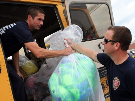 Clarksville Fire Rescue's Phillip Clouser, left, and Glenn Stewart load bags stuffed with toys on a bus Saturday at BWC's annual Toy Run.