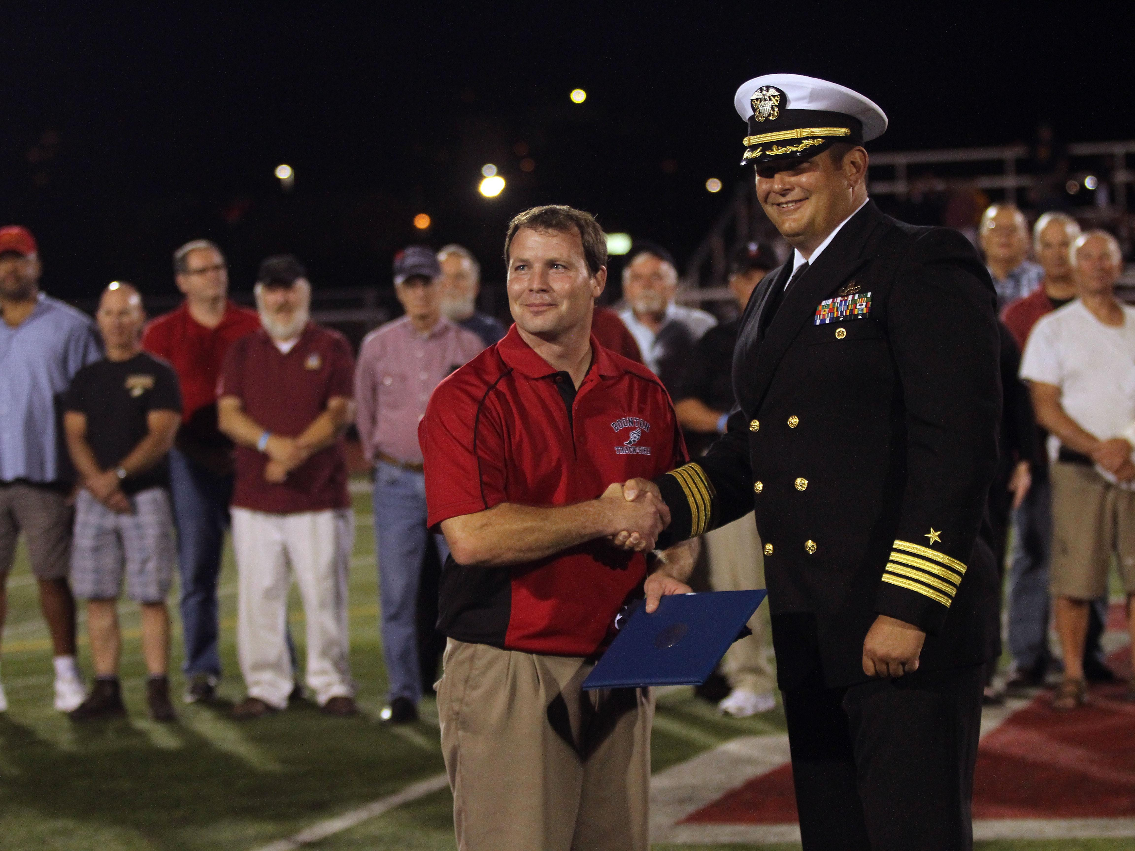 Boonton Athletic Director Dave Hughen, l, is presented an American flag flown over the Pentagon by Boonton grad, Navy Capt. Dean Muriano as Boonton High School honored its graduate military veterans during halftime of the Boonton High School football game Friday night. The vets, some of whom are still residents, others coming back from out of town, also enjoyed a tailgate party prior to the game and ceremony. September 18, 2015, Boonton, NJ.