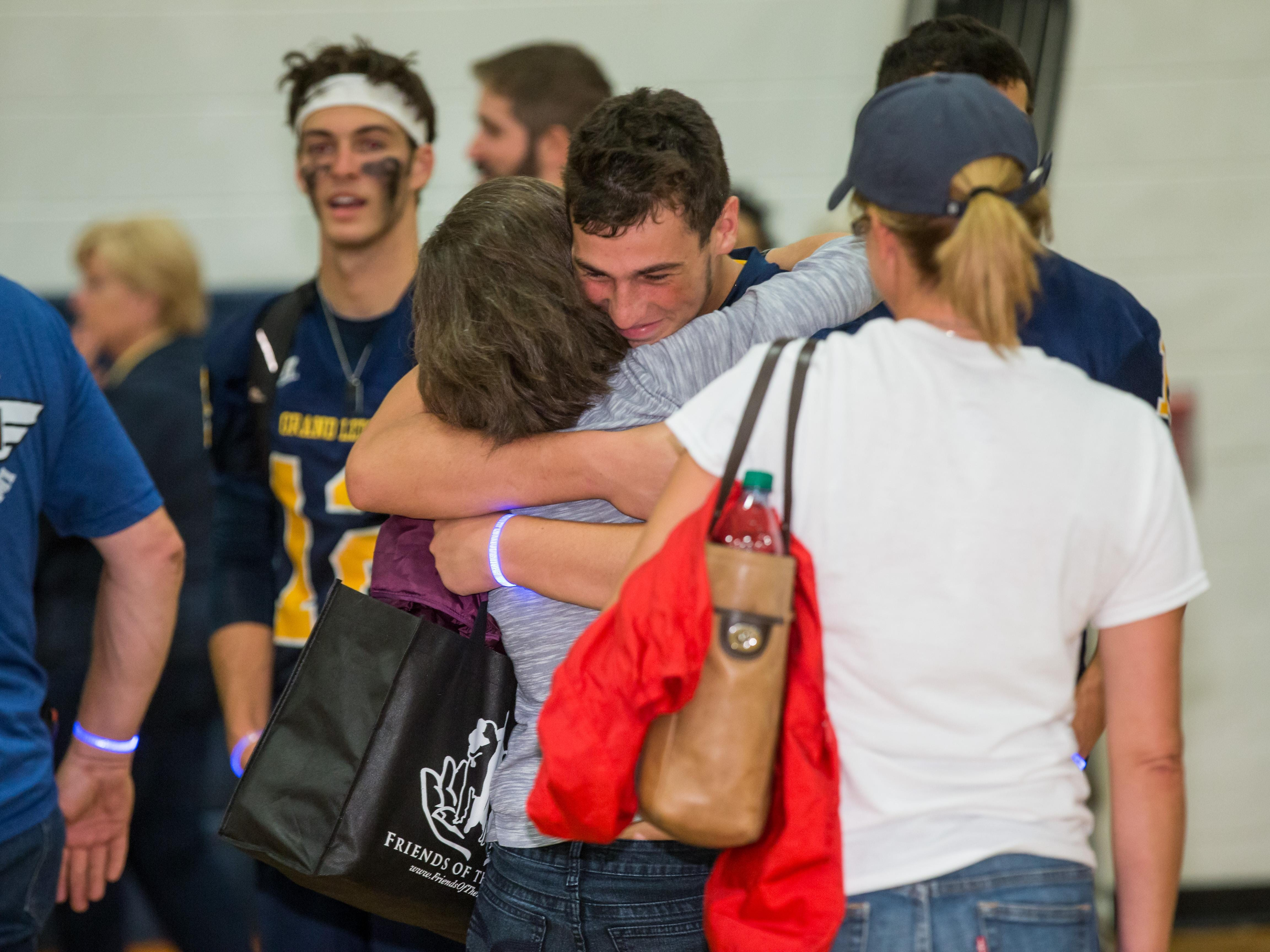 A Grand Ledge football player hugs the family member of a fallen soldier following Friday's football game against Okemos.