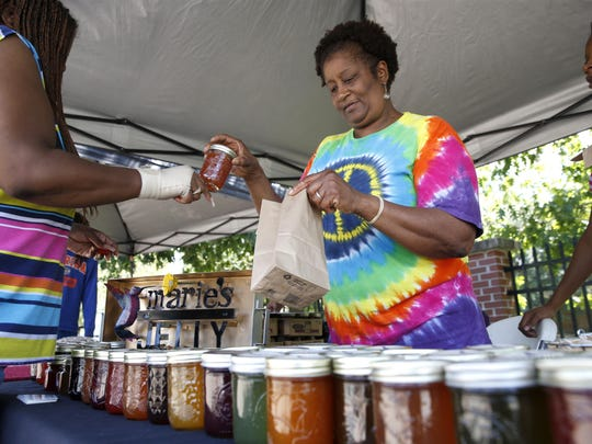 Marie Garrison sells some of her homeade jelly to a customer at the Frenchtown Heritage Market.