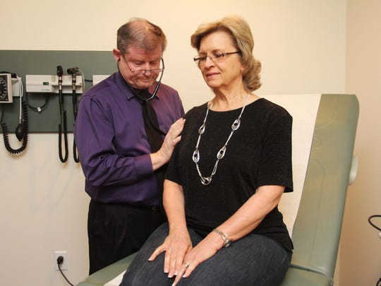 Dr. William Graham works with a patient at Bethesda Medical Care in April 2013.