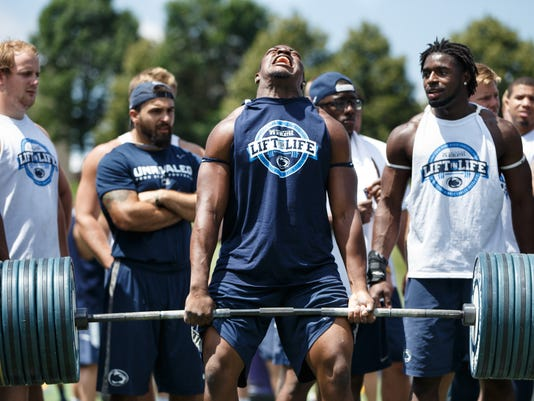 Penn State linebacker Jason Cabinda lifts weights at Saturday's Lift for Life event in State College. The 13th annual event raises funds for the Kidney Cancer Association in conjunction with Uplifting Athletes.