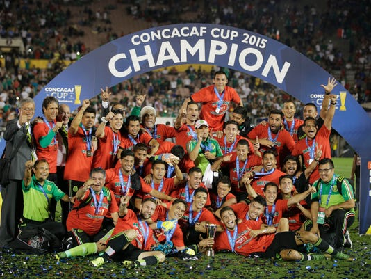 Players of Mexico pose with the CONCACAF Cup trophy after beating the US 3-2 during a playoff soccer match at the Rose Bowl Stadium, in Pasadena , Calif. Saturday, Oct. 10, 2015, (AP Photo/Jae C. Hong)