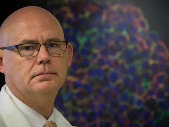 University of Delaware Professor Kenneth van Golen stands in front of a picture a magnified breast cancer cells on Sept. 9. Vice President Joe Biden on Friday is launching an effort to find a cure for cancer.