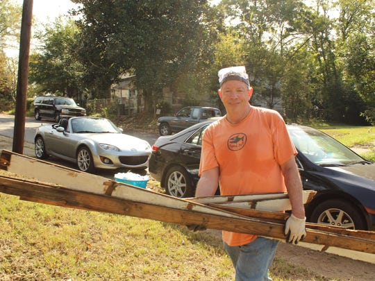 """""""Montgomery Advertiser"""" Executive Editor Tom Clifford hauls away wood removed from an old house Elm Street house that is being replaced by a new family dwelling as part of the House-to-House program. Alvin Benn/Special to the Advertiser"""