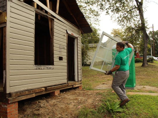 """Robert Edmonds of """"The Montgomery Advertiser"""" brings in a window to be used later as part of the rehabilitation of two abandoned houses on Elm Street as part of the House-to-House program. Alvin Benn. Special to the Advertiser"""