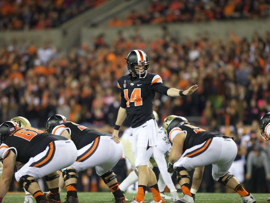 Oregon State quarterback Nick Mitchell (14) prepares to take the center snap from his older brother, Josh, during last Saturday's game against Colorado at Reser Stadium.